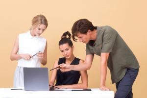 Deux professionnels informant une nouvelle employée sur ordinateur.